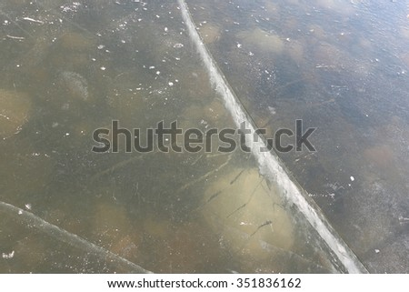 Cracks on an ice surface of the river, a natural background
