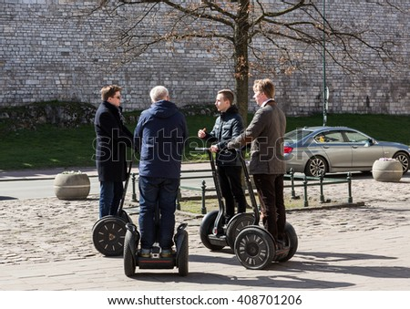 CRACOW, POLAND - APRIL 2, 2016: the serious debate of four men on Segways in Cracow. Poland - stock photo