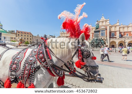 Cracow, Poland. Traditional horse carriage on the main old town market square. Cloth Hall and Mickiewicz Monument behind. - stock photo
