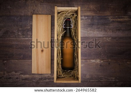 Craft beer bottle in a wooden gift box on a rustic table - stock photo