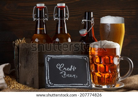Craft beer glass and vintage wooden crate with beer bottles on burlap cloth with barley seeds - stock photo