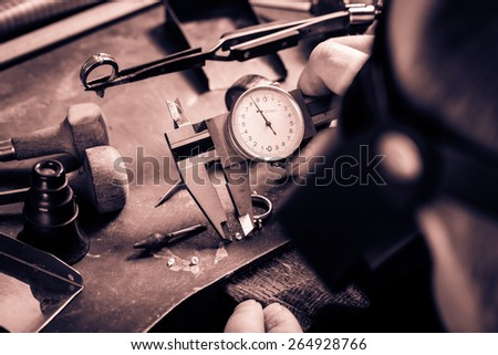 Craft jewelery making.  Measuring of the size of the diamond. Monochrome cream tone. Black and white photography. - stock photo