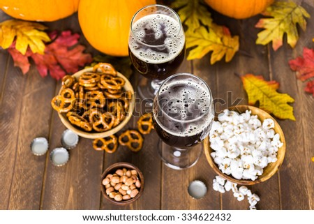 Craft pumpkin beer in beer glasses with salty pretzels and popcorn.