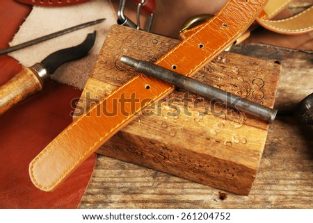 Craft tools with leather belt on table close up - stock photo