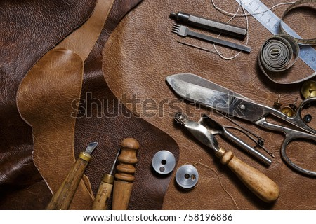 Crafting tools on natural cow leather in the tailoring workshop. Top view.
