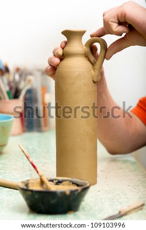 Craftsman attaching handle to the bottle made of fresh clay in pottery workshop. Shallow depth of field. Focus on handle. - stock photo