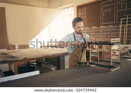 Craftsman carefully manufacturing a glass and wood display case in his workshop - stock photo