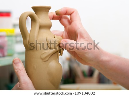 Craftsman decorating with fruit shape bottle made of fresh clay in pottery workshop. Shallow depth of field. Focus on thumb. - stock photo