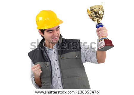 craftsman holding a golden cup - stock photo