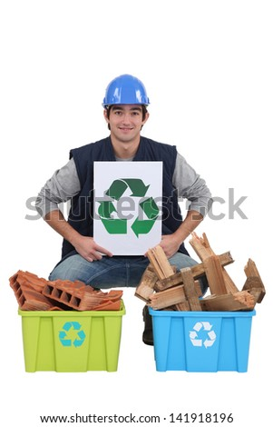 craftsman holding a recycling label over two boxes of used materials - stock photo