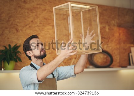 Craftsman holding up a glass and wood display case that he designed and manufactured with skill  - stock photo