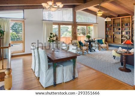 Craftsman home Living room interior beautifully staged with bamboo chairs, book shelf, rug and view windows. Stunning living room in craftsman home with dramatic wood beamed ceilings. - stock photo