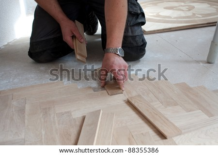 craftsman lays parquet on a construction site/craftsman lays parquet
