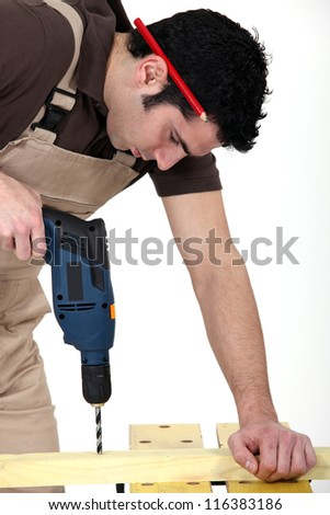 craftsman making a hole with a drill - stock photo