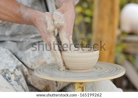 Craftsman making vase from fresh wet clay on pottery wheel hands closeup - stock photo