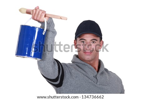 craftsman painter holding a can and a brush - stock photo