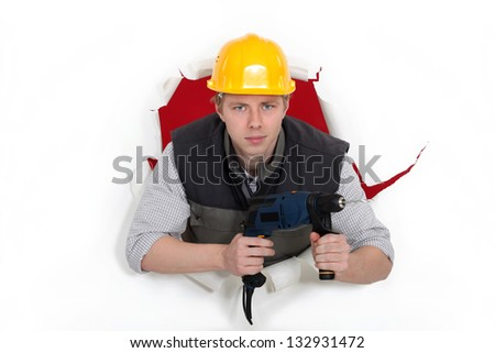 craftsman posing in the hole of paper wall and holding a drill - stock photo