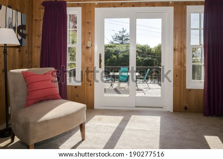 Craftsman style furnished room with french sliding glass doors leading to amazing balcony wooden deck - stock photo
