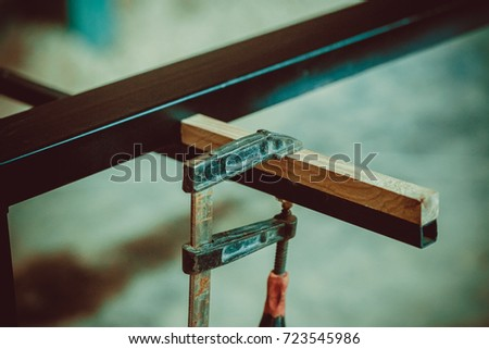 Craftsman Using Clamps Fixate Two Pieces Of Wood And Iron. The Process Of  Making Desk