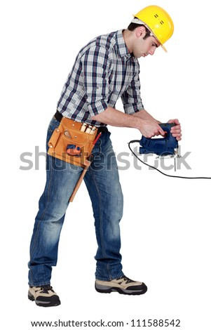 craftsman working with an electric cutter - stock photo