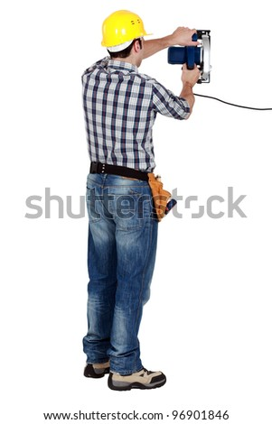 craftsman working with an electric saw - stock photo