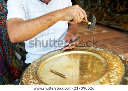 craftsman working with hammer during hand stamping or engraving decoration pattern on metal plate - stock photo
