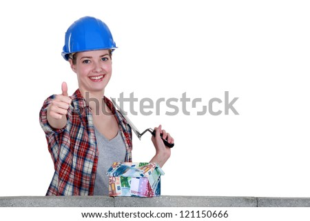 craftswoman looking at a house of bills and making a thumbs up sign - stock photo