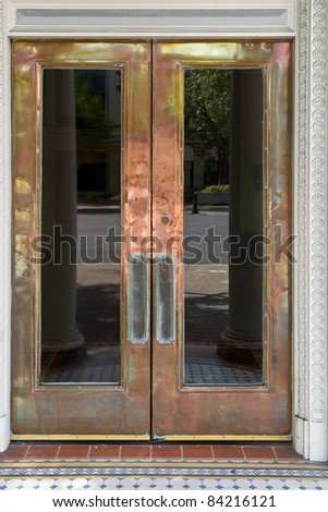 Crafty brass door with windows with street reflection - stock photo