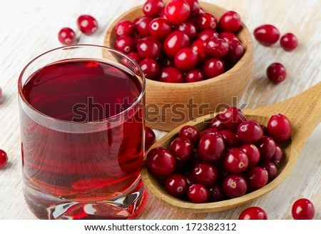 Cranberries in a  wooden spoon and glass of juice. Selective focus - stock photo