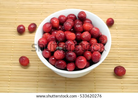 Cranberries in round white bowl and scattered berries on brown straw mat top view close up