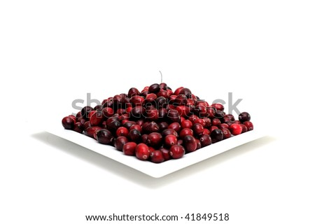 Cranberries in various shades of red on a white square plate with a single berry and stem on top, on an isolated background
