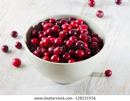 Cranberries on wooden table - stock photo