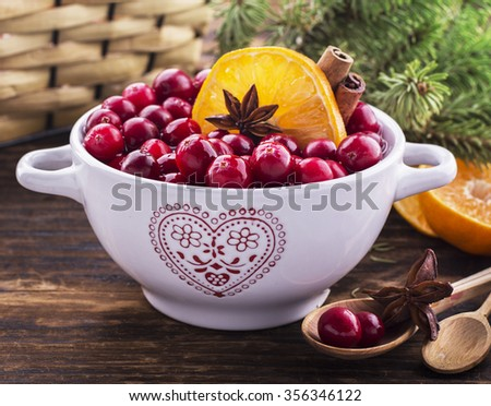 Cranberries with orange, cinnamon and star anise in a white ceramic on a dark wooden background for making cranberry sauce or jam. Selective focus. The concept is simple homemade classic cuisine - stock photo