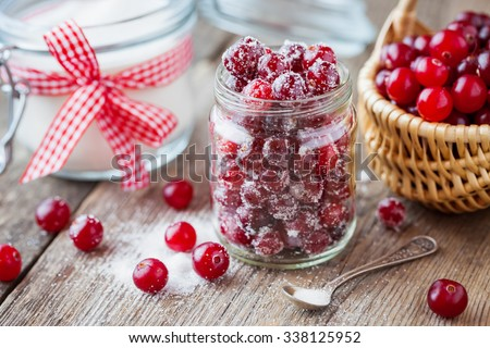 Cranberries with sugar in glass jar, basket with berries and sugar bowl on background. Selective focus. - stock photo