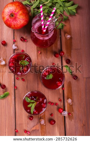 Cranberry and pomegranate cocktail with mint garnish and ice cubes. Selective focus - stock photo
