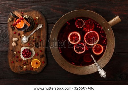 Cranberry citrus punch or mulled wine with ingredients over dark wooden table. - stock photo