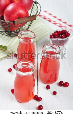 Cranberry juice in glass jars and fresh apples in vintage basket on a white wooden background - stock photo