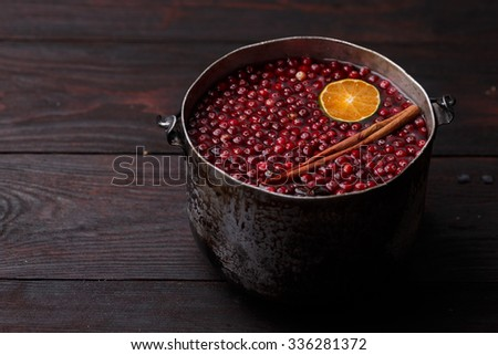 Cranberry mandarin pomegranate punch or mulled wine in a rustic aged pot over wooden backdrop - stock photo