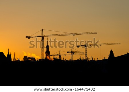 Crane and building silhouettes over sun at sunrise - stock photo