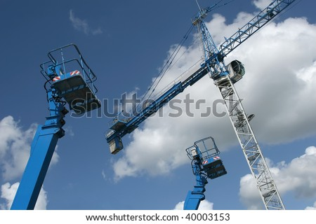 Crane and telescopic people lifts against blue sky with clouds.