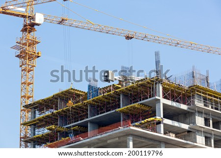 Crane and unfinished building against blue sky background - stock photo