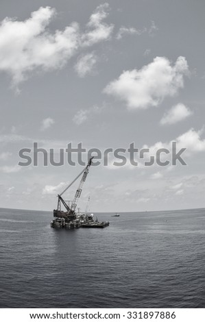 crane barge lifting heavy cargo or heavy lift in offshore oil and gas industry. Large boat working for lift piping and installation the platform. - stock photo