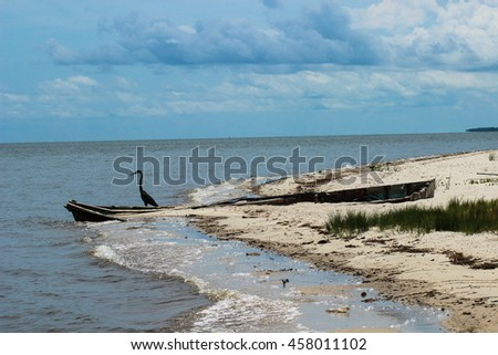 Crane by abandoned fishing boat on deserted sandy beach with cloudy blue sky in background - stock photo