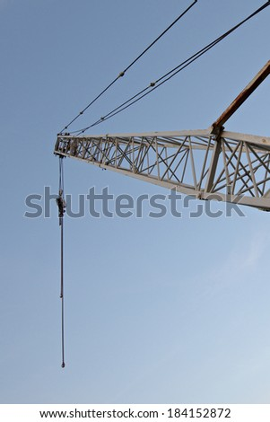 Crane derrick against blue sky - vertical format with copy space - stock photo