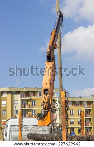 Crane hook lifting the wooden telephone pole out, replacing an old wooden telephone pole on the grounds. - stock photo