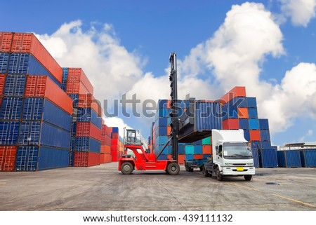 Crane lifter handling container box loading on trucks.