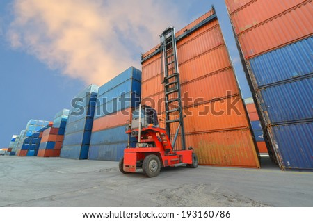Crane lifter handling container box loading to truck in import export zone - stock photo