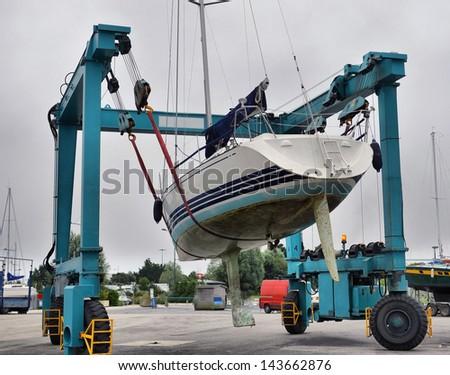 Crane lifting boats at harbor - stock photo