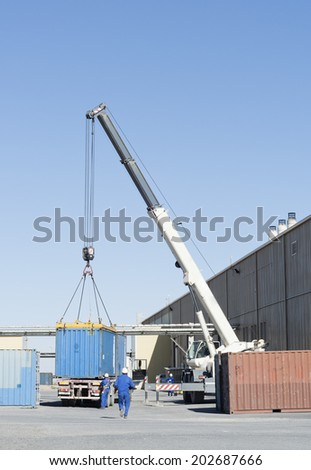 Crane load of container box up truck. - stock photo