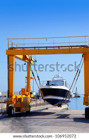 crane travelift lifting a boat on blue sky day in balearic islands - stock photo